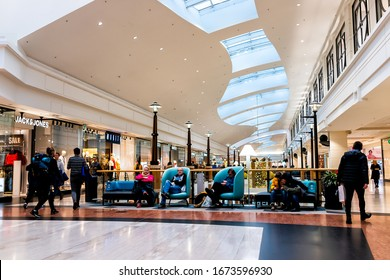 Warsaw, Poland - December 23, 2019: People relaxing resting at sitting area with couch sofa and armchairs by stores and boutique shops inside of Westfield Arkadia shopping mall with people