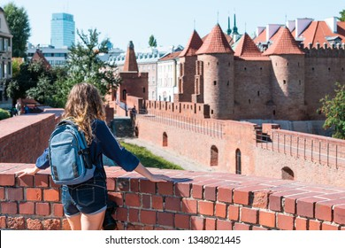 Warsaw, Poland Famous Barbican old town historic capital city during sunny summer day and red orange brick wall fortress architecture with young woman travel tourist backpack
