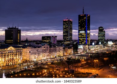 Warsaw, Poland - January 22, 2020: High angle aerial panoramic view of Warszawa cityscape skyline with centralna train station and skyscrapers buildings at night illuminated
