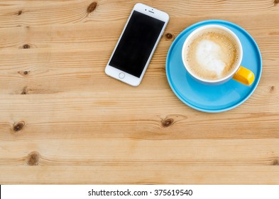 WARSAW, POLAND - JANUARY 25, 2016: silver Apple iPhone 6 on a wooden desk next to a coffee in colorful Duka Tebuske cup