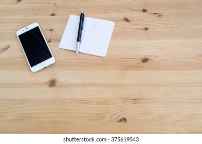 WARSAW, POLAND - JANUARY 25, 2016: silver Apple iPhone 6 on a wooden desk next to a notepad and pen