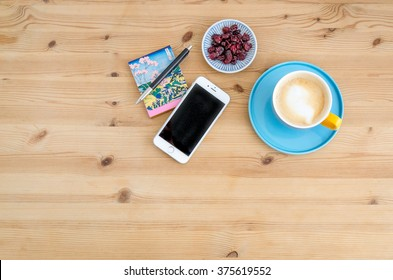 WARSAW, POLAND - JANUARY 25, 2016: silver Apple iPhone 6 on a wooden desk next to a notepad, pen and frothed coffee in a colorful Duka Tebuske cup