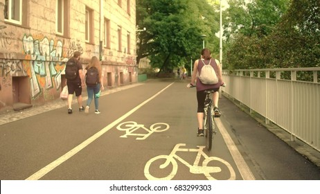 WARSAW, POLAND - JULY 11, 2017. Young woman with backsack riding her bicycle along urban bike road