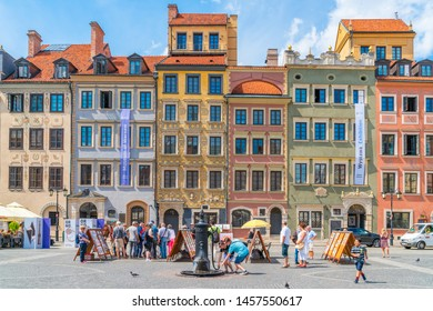 WARSAW, POLAND - JULY 19, 2019: Visitors enjoy summer day in the Warsaw Old Town Square, a busy square lined with burgher houses and upscale Polish eateries.