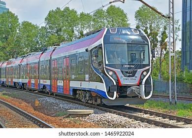 WARSAW, POLAND - JULY 20, 2019 - A Newag 39WE train, operated by Warszawska Kolej Dojazdowa (WKD), on the suburban light railway line to Warsaw, approaching Warszawa Zachodnia station