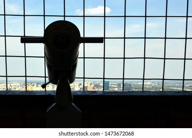 Warsaw, Poland - July 2019: Silhouette of the observation telescope on the observation terrace / deck located on the 30th floor of Palace of Culture and Science. View through the barred windows.