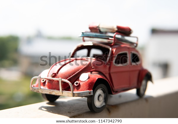 Warsaw, Poland, July 21, 2018 Old red VW Volkswagen Beetle toy car with surfboard and lifebelt on the roof, time for holidays, rest, relax on way to your dream vacation in summer, blurred background