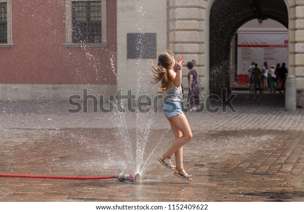 WARSAW, POLAND - JULY 31 2018: Hot summer day. Girl is playing in an improvised fountain at Castle Square.