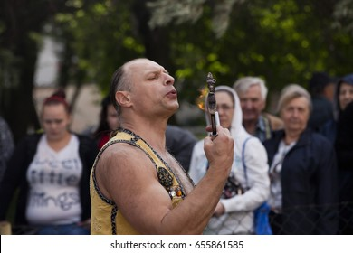 """WARSAW, POLAND, June 1: Juggler with blazing torches during a performance on """"Children's Day"""" party June 1, 2017 in Warsaw, Poland."""