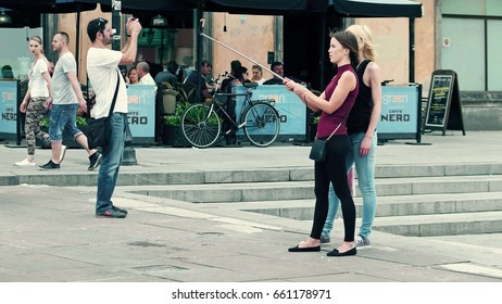 WARSAW, POLAND - JUNE 10, 2017. Young women make selfies in a tourist place, old town