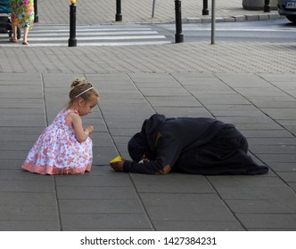 Warsaw, Poland - June 15, 2019: little blonde girl in pink dress gives money to a homeless man begging for change on a pavement. Authentic street scene from Warsaw