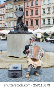 WARSAW, POLAND - June 2, 2014:Old man playing on acordeon near the Statue of Syrenka (Mermaid of Warsaw, sculptor Konstanty Hegel, circa 1855 ) at Old Town Market. UNESCO World Heritage Site