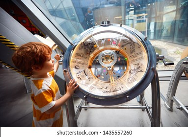 WARSAW, POLAND - June 20, 2019: Kid testing the bacterie universe globe model in the Copernicus Science Centre in Warsaw, Poland