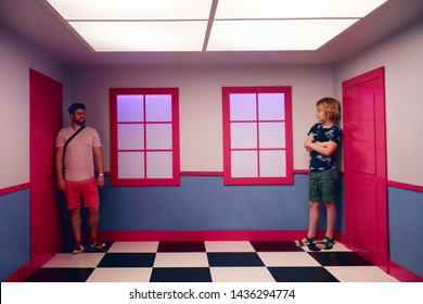 WARSAW, POLAND - June 20, 2019: Family exploring the laws of perspective, where the apparent change in size is associated with the degree of remoteness from the observation point. Copernicus Centre