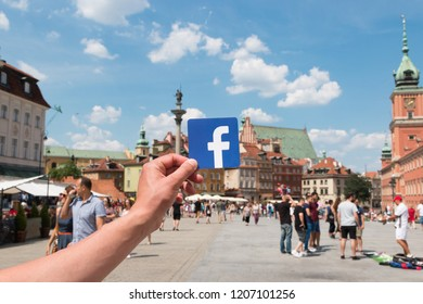 Warsaw, Poland. June, 2018. Logo Facebook and the city on the background. Concept. Man holds the logo of a popular company.