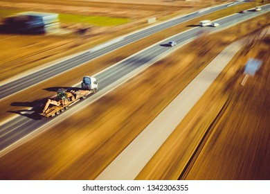 Warsaw, Poland - Mar 18, 2019: Lowloader low loader truck with excavator backhoe lodaer machine transportation high speed street road highway