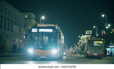 WARSAW, POLAND - MARCH 1, 2018. City buses driving along Nowy Swiat street in the evening