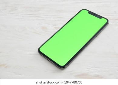 WARSAW, POLAND - March 15, 2018:  Iphone X smartphone on white wooden desktop.