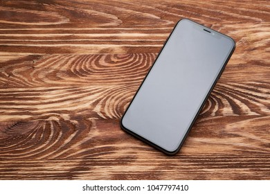 WARSAW, POLAND - March 15, 2018: New Iphone X smartphone on wooden desktop
