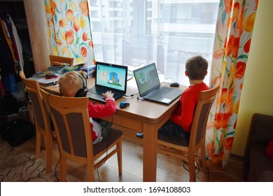 Warsaw, Poland - March 20, 2020: Two boys doing homework during the coronavirus epidemic. Ongoing isolation causes weariness and sadness. Schools  closed, people are not allowed to leave their homes.