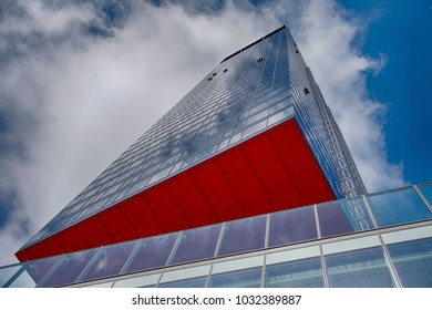 WARSAW, POLAND - MARCH 26, 2017: A dramatic view of a modern office building with red details is cantilvered out over the street in Warsaw, Poland.