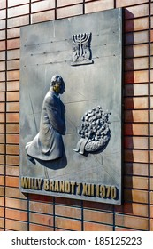 WARSAW, POLAND - MARCH 29, 2014: Bronze Plaque by W. Czechowska-Antoniewska, a part of unveiled Dec. 6, 2000 memorial commemorates the Willy Brandt laid a wreath at the Memorial to the Ghetto Heroes