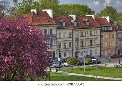 WARSAW, POLAND - MAY 01, 2017, Colorful houses near the fortress wall in the old town in Warsaw. Cherry blooms