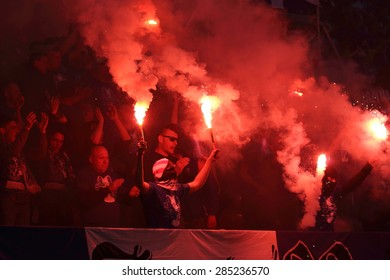 WARSAW, POLAND - MAY 02, 2015: Lech Poznan ultra supporters burn flares during Polish Cup Final football match between Legia Warsaw and Lech Poznan at the National Stadium in Warsaw.