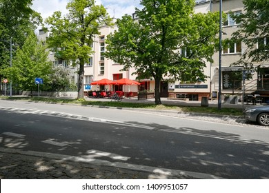 Warsaw, Poland - May 03, 2019: The street, large trees and tenement houses are the district of Saska Kepa. Across the street there is an outdoor restaurant with red chairs and umbrellas.