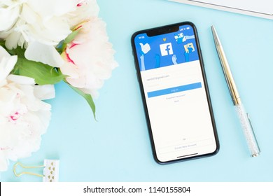WARSAW, POLAND - MAY 13, 2018: New Iphone X modern mobile phone with facebook page on blue desk with flowers, styled flat lay scene