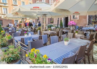 Warsaw, Poland - may, 2018: cityscape. street cafe with many served tables in architecture street background in historical center of Warsaw, Poland