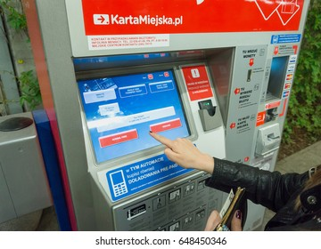 WARSAW, POLAND - MAY 22, 2017: Woman buying public transportation tickets from machine in Warsaw. Public transportation in Warsaw consists of tram, train, bus and subway.