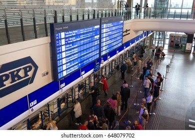 WARSAW, POLAND - MAY 24, 2017: Timetable in Warsaw train station and people in queue for tickets. Warszawa Centralna is the primary railway station in the capital city.