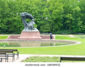 WARSAW, POLAND - MAY 24, 2017: Frederic Chopin statue in Lazienki Park in Warsaw with two tourists looking at it. Chopin was a Polish composer and pianist.