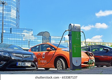 WARSAW, POLAND - MAY 30 - Electric cars, including a taxi, connected by a plug (plug-in) to a charge station for electric cars, with a glass skyscraper in the background, on May 30, 2017 in Warsaw