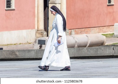 Warsaw, Poland May 31, 2018: The nun walks through plac Zamkowy (Zamkowy square) in front of The Royal Castle of Warsaw, Poland
