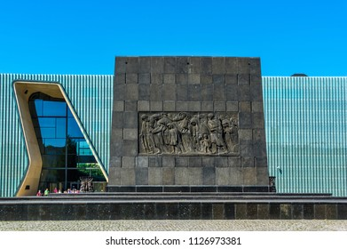 Warsaw, Poland - May 31, 2018:  Iconic Monument to the Warsaw Ghetto Heroes and the modern building of the Museum of the History of Polish Jewish in the background.