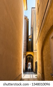 Warsaw, Poland narrow alley street near old town market square with historic town architecture and orange yellow color with arch way