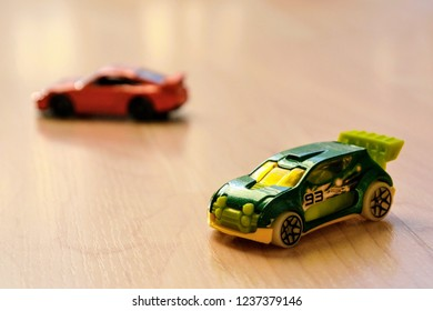 Warsaw, Poland - November 17 2018: Miniature, colorful toy cars on the wooden floor. Colorful toy cars - Hot Whells brand