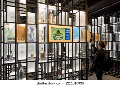 Warsaw, Poland - Oct 20, 2018: A visitor taking a picture of old Vodka bottles in the Warsaw Vodka Museum.
