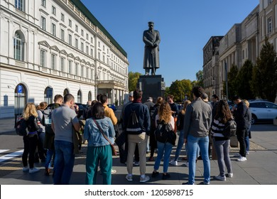 Warsaw, Poland - Oct 6, 2018: Group of tourists listening to a tour guide at The Jozef Pilsudski Monument in Warsaw, He was  a military leader, Marshal of Poland.