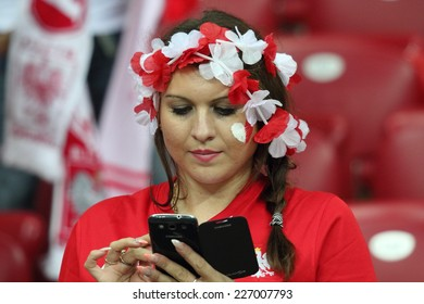 WARSAW, POLAND - OCTOBER 11, 2014: Young unidentified fan of the Polish national football team writes a text message during the UEFA EURO 2016 qualifying match of Poland vs. Germany