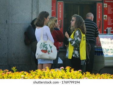 Warsaw, Poland - October 15, 2019: Young women talking to an activist from Amnesty international in the middle of the sidewalk