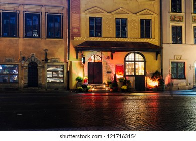 Warsaw, Poland - October 19 2018: U Fukiera restaurant Halloween decoration facade. Night view of traditional Polish dining illuminated entrance with candle lights, pumpkins and fresh flowers.