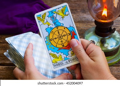 WARSAW, POLAND - OCTOBER 2, 2015: Fortuneteller holding Tarot fortune wheel card of one of the most popular occult Tarot deck dating back 1910