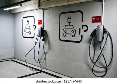 Warsaw, Poland - October 20 2018: Tesla electric vehicle plug-in car charging station in the underground parking lot. Electric car sign in parking area.