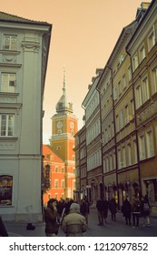 Warsaw, Poland - October 5 2018: A view of the royal castle in Warsaw from an old town street in low key warm tones