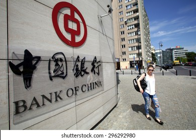 WARSAW, POLAND - SATURDAY, JUNE 6, 2015: A pedestrian walks past the offices of the Bank of China in Warsaw. Bank of China Limited is one of the 5 biggest state-owned commercial banks in China.