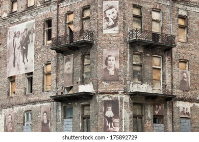 WARSAW, POLAND - SEPTEMBER 1, 2012: Holocaust memorial - a building from Warsaw ghetto with pictures of jews on the facade.
