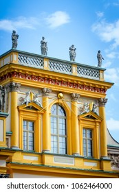 WARSAW, POLAND - SEPTEMBER 13, 2009: Wilanow Royal Palace central yellow facade part architectural details with golden Sun rays